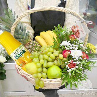 Фрукты, цветы и напиток в белой корзине